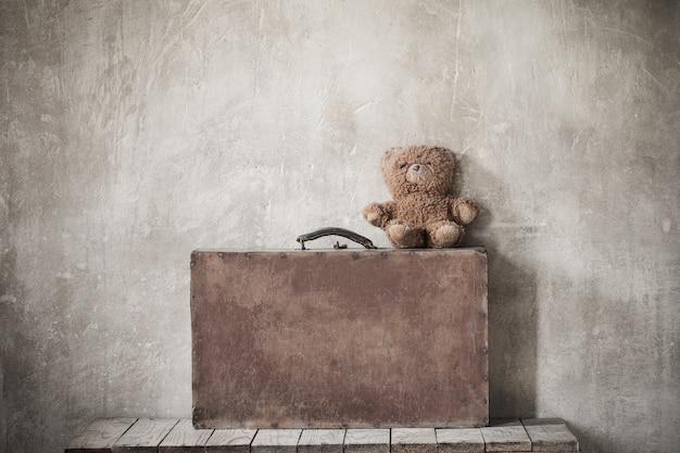 Ours en peluche brun et vieille valise