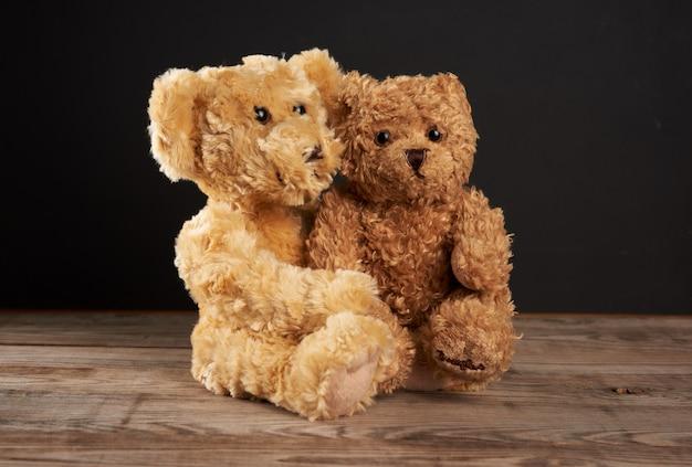 Ours en peluche bruns assis les uns à côté des autres