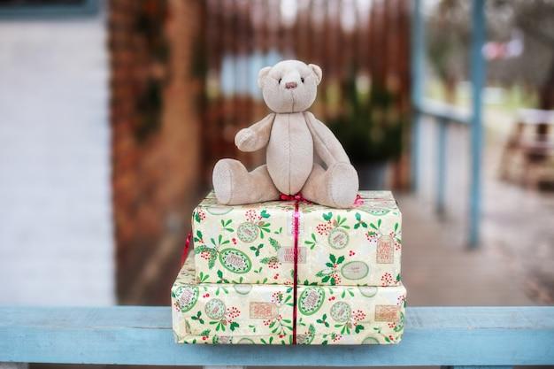 Ours en peluche et cadeaux de noël sur le porche de la maison un jour d'hiver