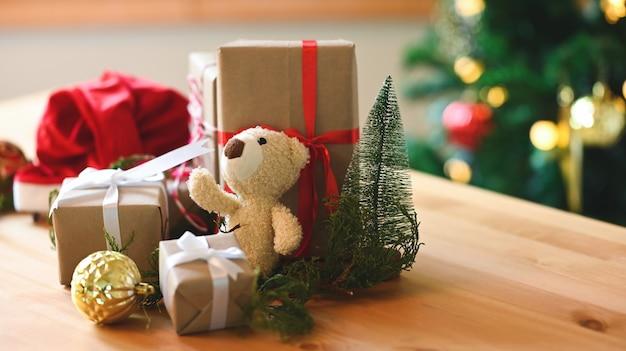 Ours en peluche et cadeaux de noël sur table en bois.