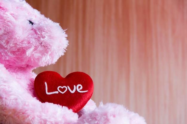 Ours en peluche avec coeur sur fond de bois, saint valentin