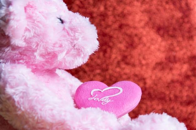 Ours en peluche avec coeur sur fond rouge, saint valentin