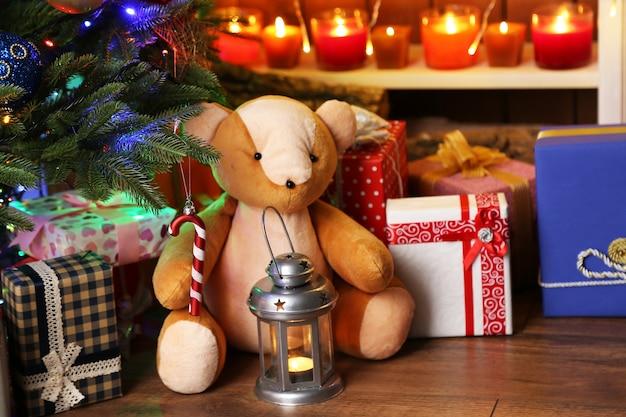 Ours en peluche et coffrets cadeaux près de l'arbre de noël, gros plan