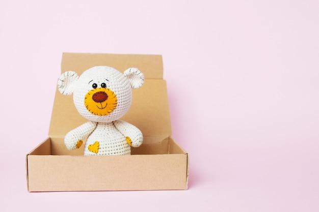 Ours en peluche dans une boîte artisanale isolée sur un fond rose. fond de bébé. espace de copie, vue de dessus