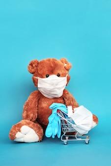 Ours en peluche dans un masque chirurgical, un gel désinfectant et des gants de laboratoire bleus