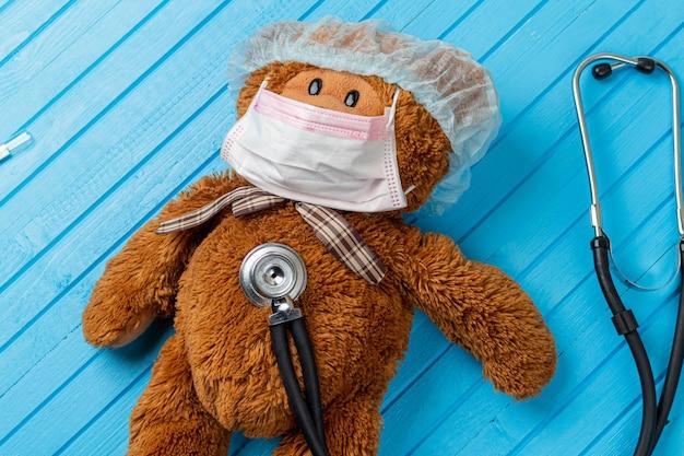 Ours en peluche dans un masque médical de protection et un stéthoscope