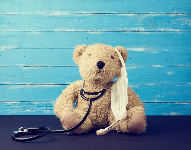 L'ours en peluche est assis dans un masque médical blanc et un stéthoscope noir est suspendu à son cou