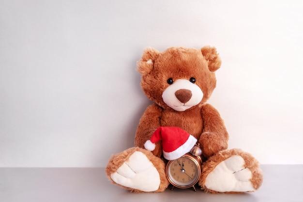 Ours en peluche est assis et garde le réveil en chapeau rouge sur fond blanc