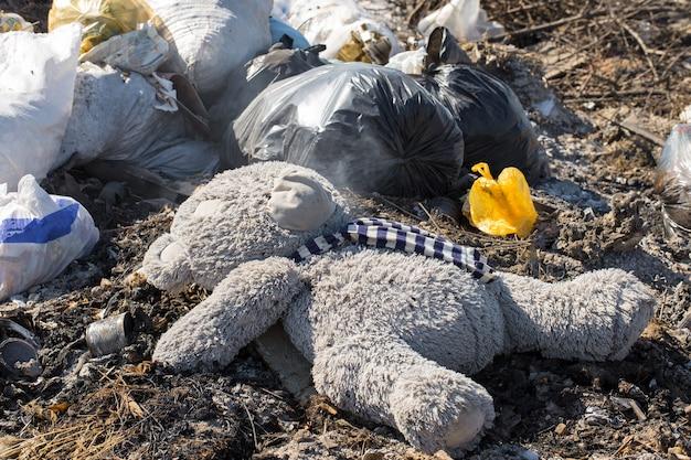 Un ours en peluche est jeté au milieu d'une décharge d'ordures fumante