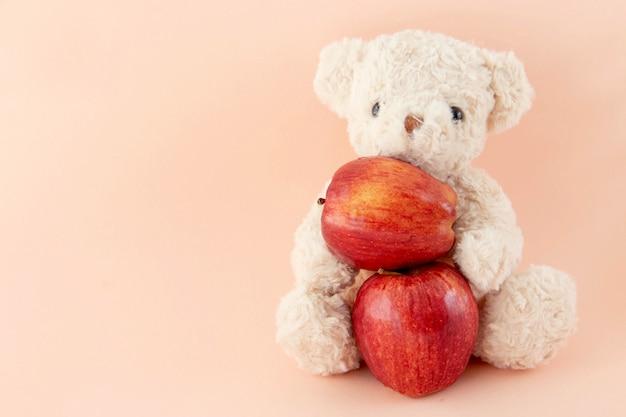 L'ours en peluche est en train de manger une pomme rouge