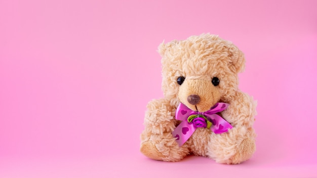 Ours en peluche sur fond rose. le concept du cadeau.