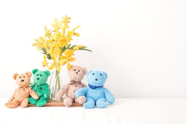Un ours en peluche de groupe prendre une photo avec des fleurs d'orchidées, la relation est un ami pour toujours