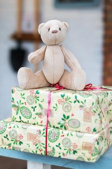Ours en peluche jouet et cadeaux de noël sur le porche de la maison un jour d'hiver