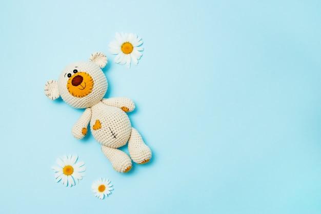 Ours en peluche à la main amigurumi avec marguerites isolé sur un fond bleu. fond de bébé. espace de copie, vue de dessus.