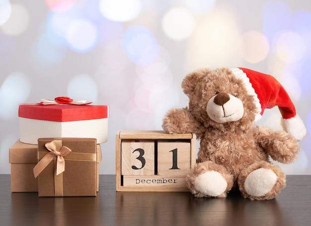 Ours en peluche marron et une pile de différentes boîtes en carton pour des cadeaux sur une table noire