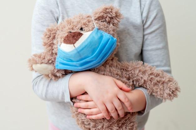 Ours en peluche avec masque de protection dans les mains de l'enfant