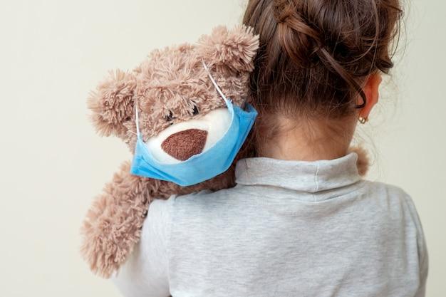Ours en peluche avec masque de protection sur l'épaule de l'enfant