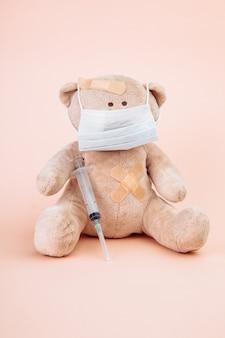 Ours en peluche avec un masque et une seringue