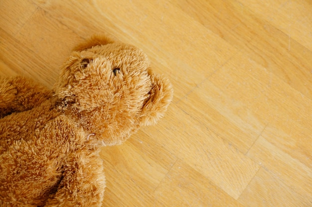 Ours en peluche mignon brun sur le plancher en bois
