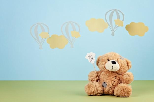 Ours en peluche mignon sur le fond bleu pastel avec des nuages et des ballons