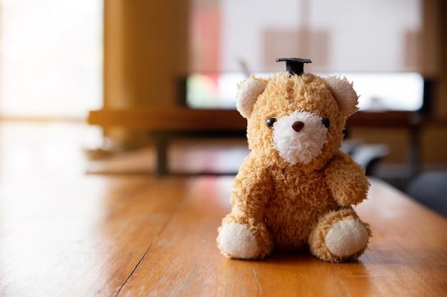 Ours en peluche portant un chapeau de célibataire sur une table en bois.