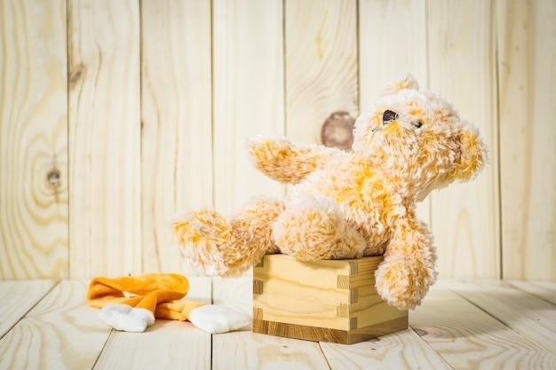 Ours en peluche seul sur boîte bois sur fond de bois