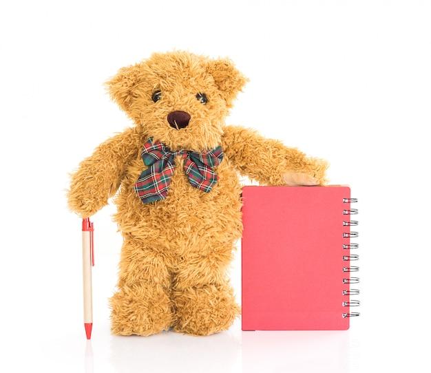 Ours en peluche avec un stylo sur un cahier rouge vierge