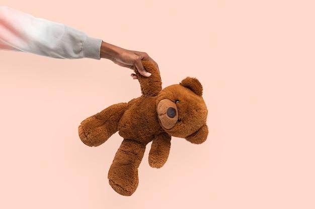 Ours en peluche tenu par une main pour une campagne caritative