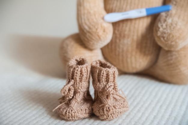 Ours en peluche et test de grossesse positif bouchent ours en peluche pour enfants, bottillons, test.