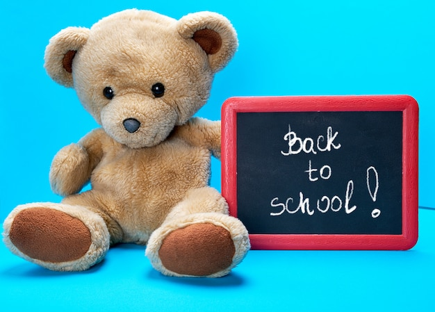 Ours en peluche tient cadre rouge avec des mots écrits à la craie de retour à l'école
