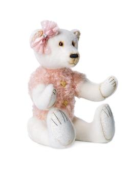 Ours polaire en peluche avec un papillon rose sur la tête sur fond blanc