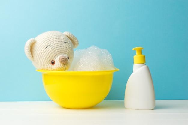 Un ours en tricot de bain et une bouteille de détergent.