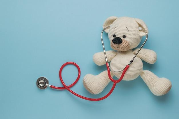 Ours tricoté mignon avec un stéthoscope rouge sur fond bleu.