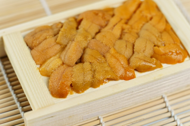 Oursin japonais dans un plateau en bois, ingrédients de sushi et sashimi