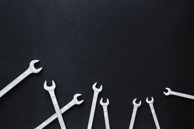 Outil d'artisan clé sur fond noir, vue de dessus, mise à plat, copyspace