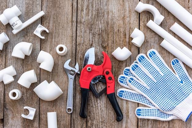 Un outil de coupe de tuyau avec des gants et une clé à molette.