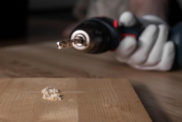 Outil de forage à tarière en gros plan sur le trou fait dans la surface en bois, gros plan.