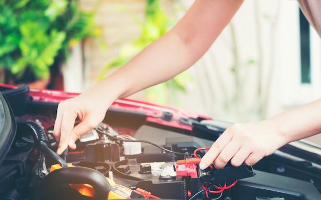 Outil de gros plan et main de femmes réparant une voiture lors d'une recherche de la cause du problème