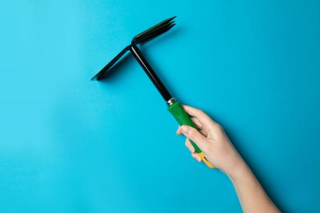 Outil de houe de jardin dans une main féminine pour le potager