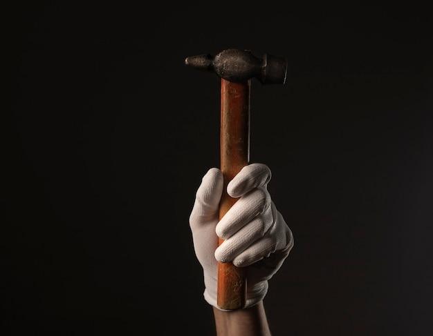Outil marteau ancien rétro vertical avec manche en bois dans la main masculine dans des gants de construction blancs en gros plan sur fond noir.