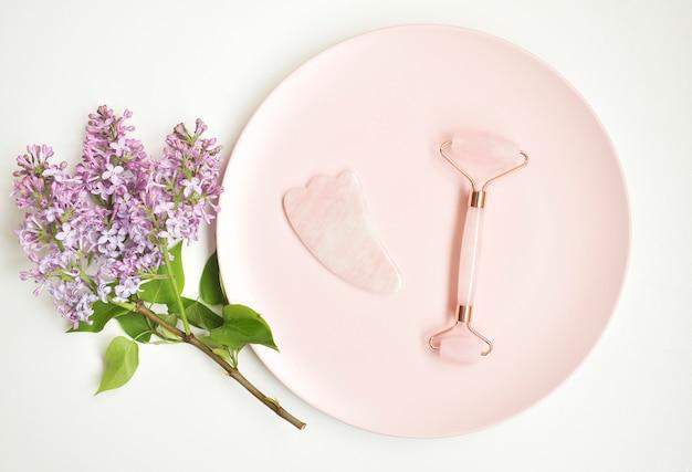 Outil de massage à la gouache rose dans une plaque rose avec des fleurs violettes