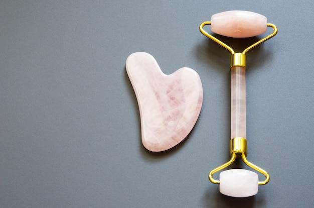 Outil de massage rose gua sha. rouleau en quartz rose. soins de la peau du visage à domicile, thérapie anti-âge et lifting. vue de dessus.
