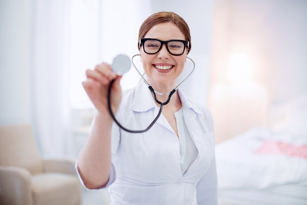 Outil de médecins. femme médecin expérimentée et attrayante restant sur un arrière-plan flou tout en souriant et en montant le stéthoscope