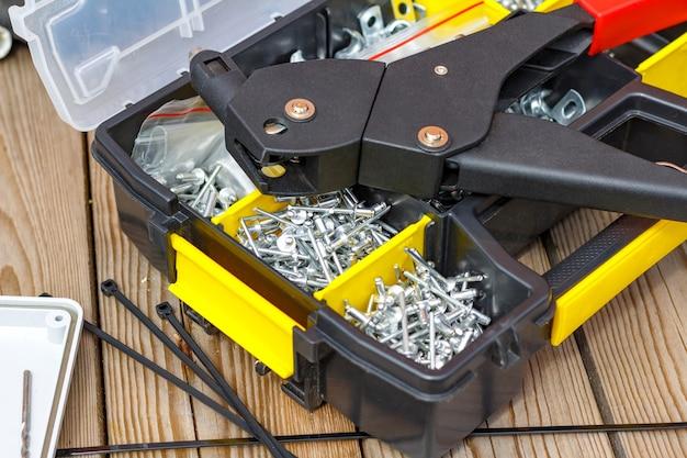 Outil à riveter et rivets de différentes tailles dans la boîte de rangement