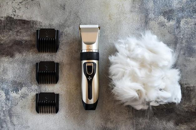 Outil de toilettage. tondeuse à cheveux et laine de chat ou de chien allongée sur fond de béton. garde d'animaux à domicile.