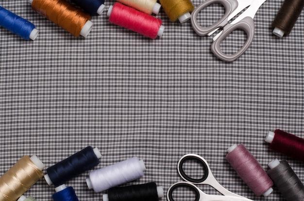 Outils et accessoires pour la couture. fil à coudre, ciseaux sur gris