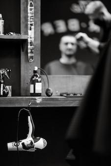 Les outils d'un barbier sur le bureau devant le miroir
