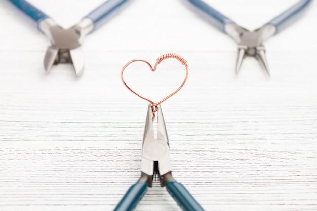 Outils de bijoux sur table en bois blanc. coeur en fil de cuivre. enroulement de fil