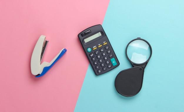 Outils de bureau. agrafeuse, calculatrice, loupe sur un pastel bleu-rose.