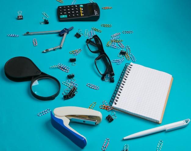 Outils de bureau, papeterie. agrafeuse, calculatrice, loupe, trombones, cahier, boussole sur bleu.